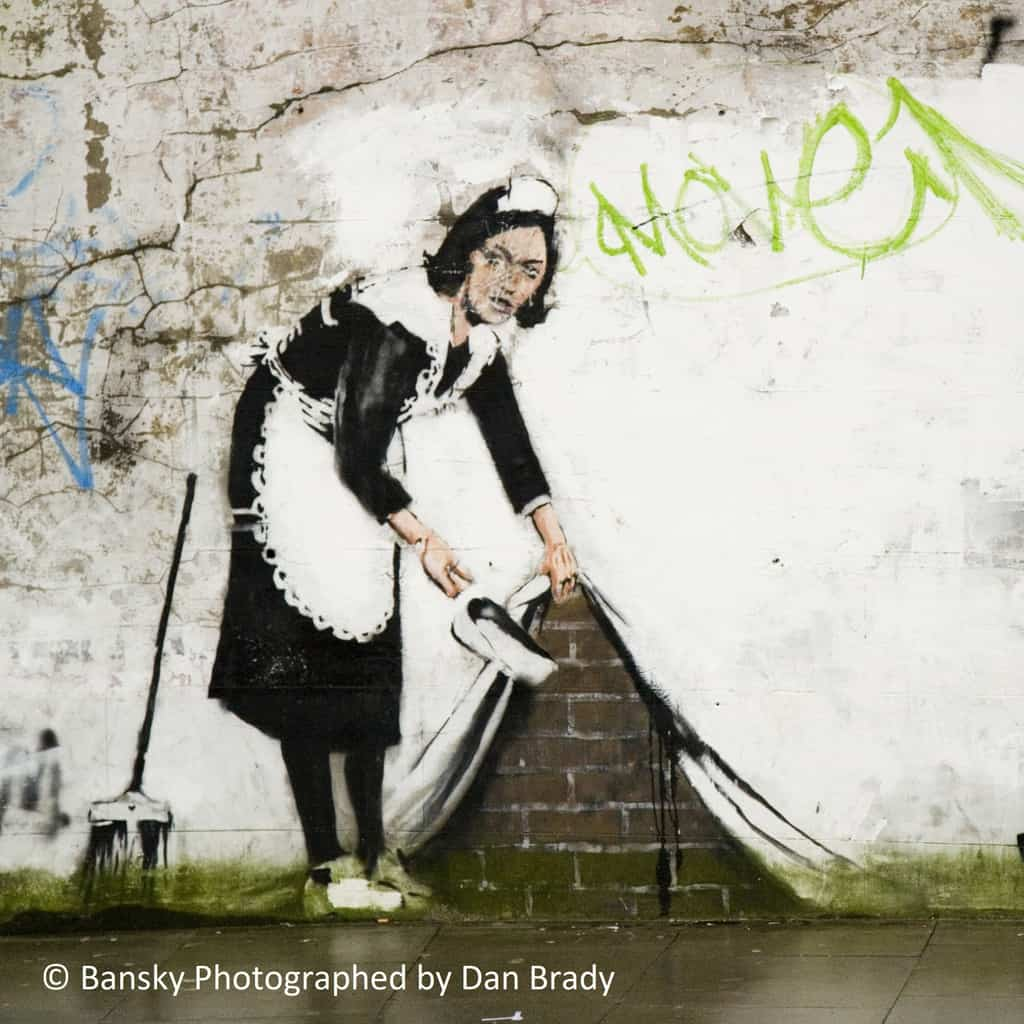 Art in Placemaking. A photography of the urban graffiti art piece by Banksy called, Street Cleaner. The illustration shows a maid appearing to hold up the wall to sweep dirt underneath.