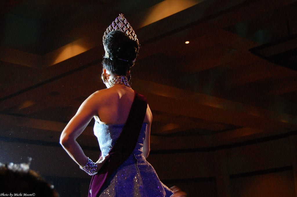 Taken from backstage point of view, a beauty queen, wearing a tiara and sash, steps into the spotlights on centre-stage to accept her award.